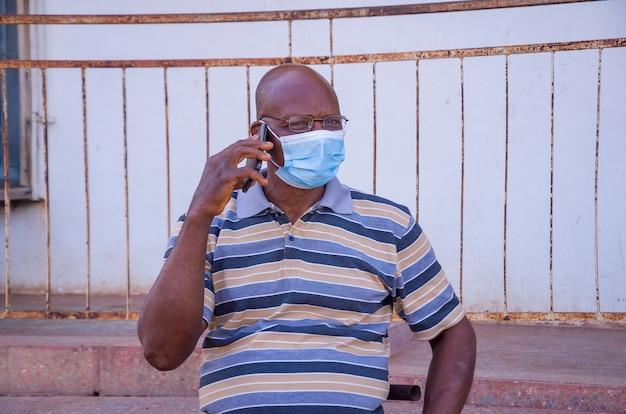 Bonito homem idoso africano usando máscara facial de prevenção, evitou o surto na sociedade sentindo-se animado com a ligação que está fazendo com seu celular.