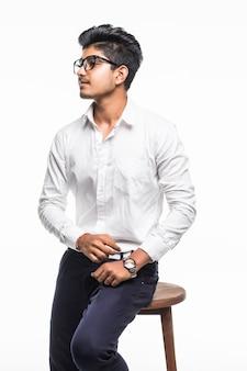 Bonito homem indiano bonito sentado em uma cadeira e relaxante, isolado para parede branca