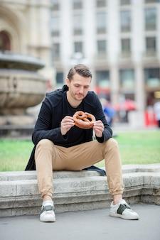 Bonito, homem jovem, segurando, pretzel, e, relaxante, parque