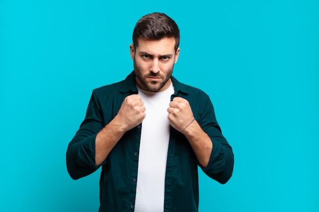 Bonito homem loiro adulto parecendo confiante, zangado, forte e agressivo, com punhos prontos para lutar em posição de boxe