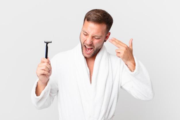 Bonito homem loiro parecendo infeliz e estressado, gesto de suicídio fazendo sinal de arma. conceito de barbear