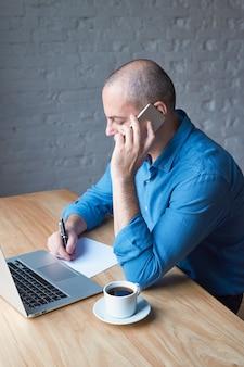 Bonito homem maduro bonito escreve em uma folha de papel e fala em um telefone celular, senta-se em um computador, laptop