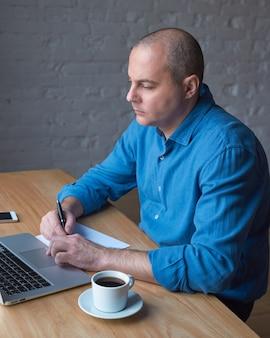 Bonito homem maduro bonito escreve em uma folha de papel e olha para a tela do computador, laptop.