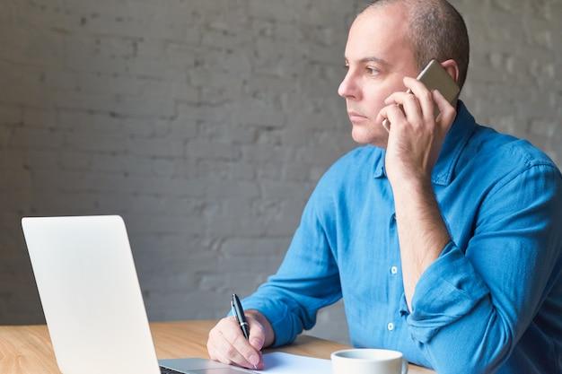 Bonito homem maduro bonito olha pela janela e falando no celular, sentado no computador, laptop.
