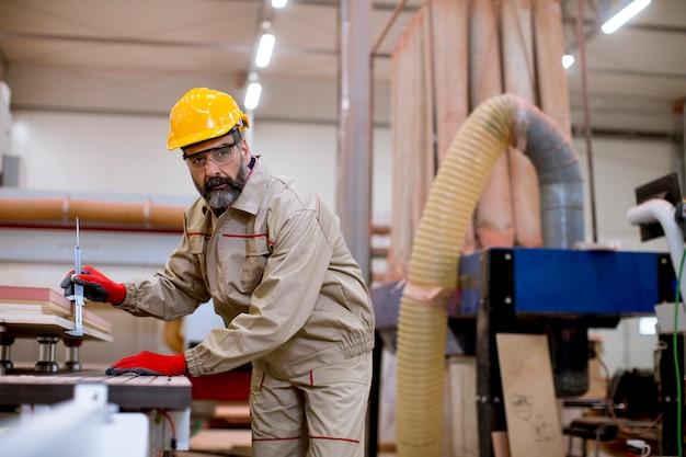 Bonito homem maduro, trabalhando na fábrica de móveis