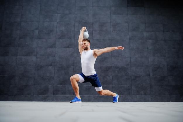 Bonito homem musculoso caucasiano em shorts e camiseta fazendo lunges e segurando o sino de chaleira. no fundo é parede cinza.