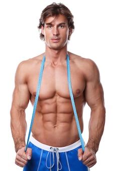 Bonito homem musculoso com fita métrica