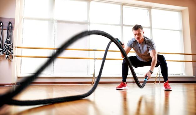 Bonito homem musculoso está fazendo exercício de corda de batalha enquanto trabalhava no ginásio