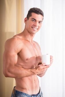 Bonito homem musculoso está segurando uma xícara de chá.