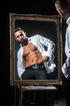Bonito homem musculoso ou atleta cara com corpo sexy de fisiculturista com torso, barriga, tanquinho, tem barba na cara séria em calças, camisa branca perto de espelho vintage isolado no fundo preto