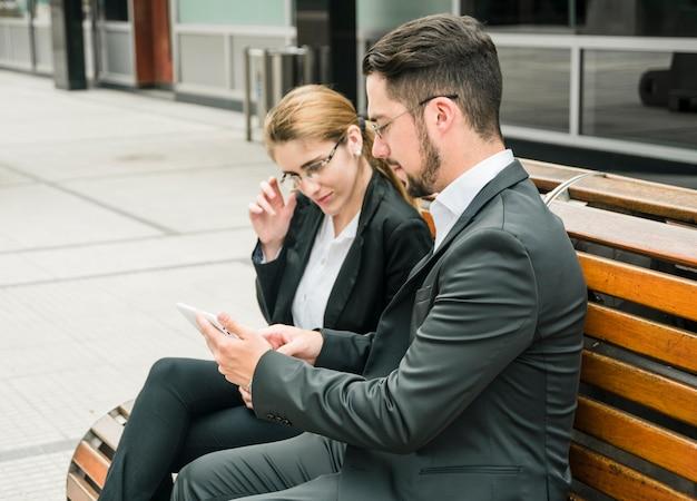 Bonito, homem negócios, mostrando, algo, ligado, telefone móvel, para, dela, colega
