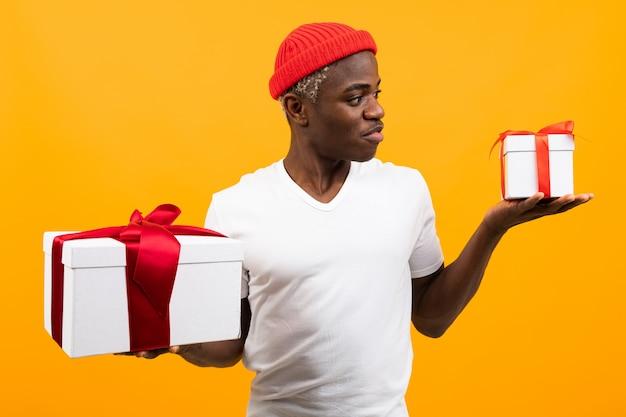 Bonito homem negro africano surpreso com um sorriso em uma camiseta branca detém duas caixas de presente com uma fita vermelha para um aniversário em um estúdio amarelo