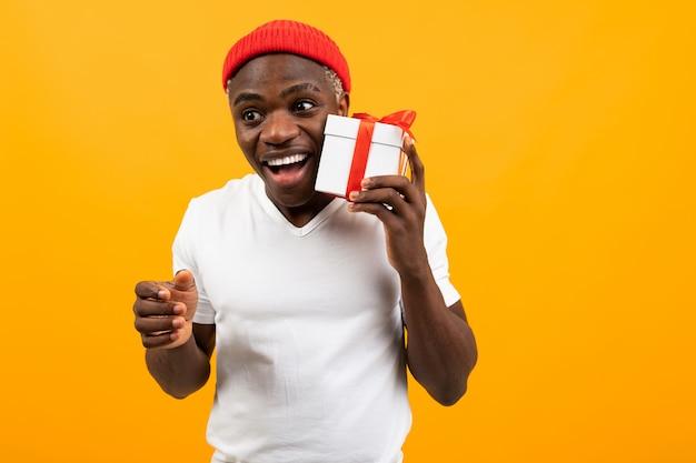 Bonito homem negro africano surpreso com um sorriso em uma camiseta branca segura uma caixa um presente com uma fita vermelha para um aniversário em um estúdio amarelo