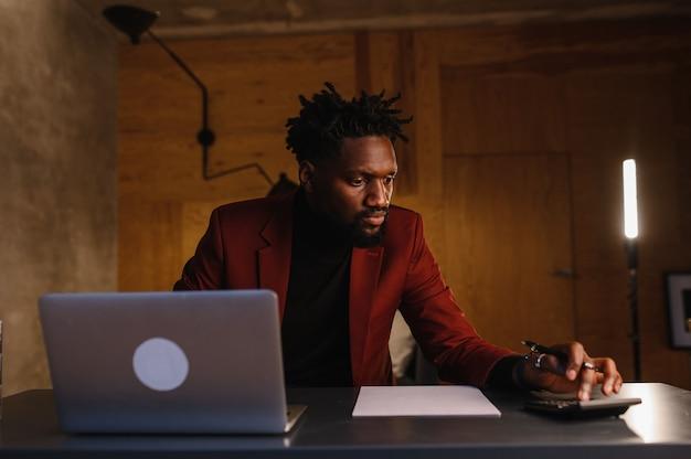 Bonito homem negro afro-americano trabalhando em um laptop enquanto está sentado atrás de uma mesa em uma aconchegante sala de estar freelancer trabalhando em casa