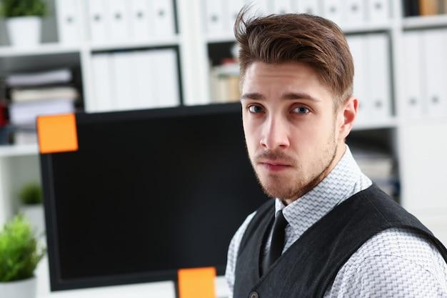 Bonito homem sorridente de terno e gravata fica no escritório