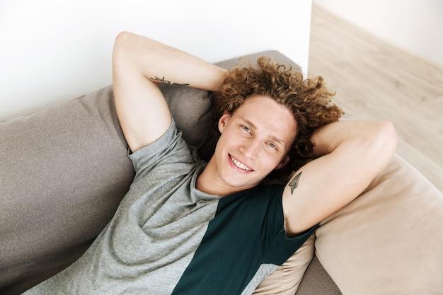 Bonito homem sorridente encontra-se no sofá