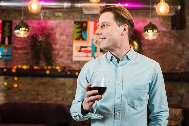 Bonito homem sorridente no bar com um copo de vinho