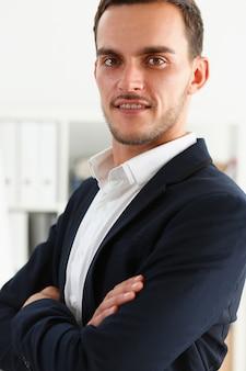 Bonito homem sorridente no terno ficar no escritório