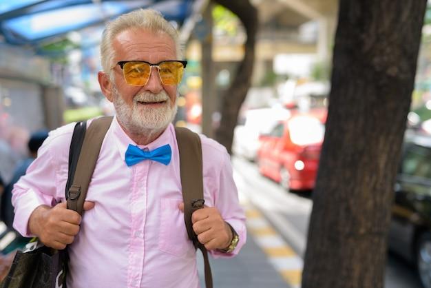 Bonito homem turista sênior explorando a cidade de bangkok, tailândia