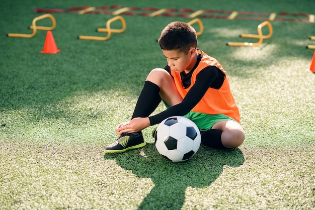 Bonito jogador de futebol de 13 anos na cobertura verde artificial do campo de esporte ao ar livre e amarrando o cadarço nas botas.