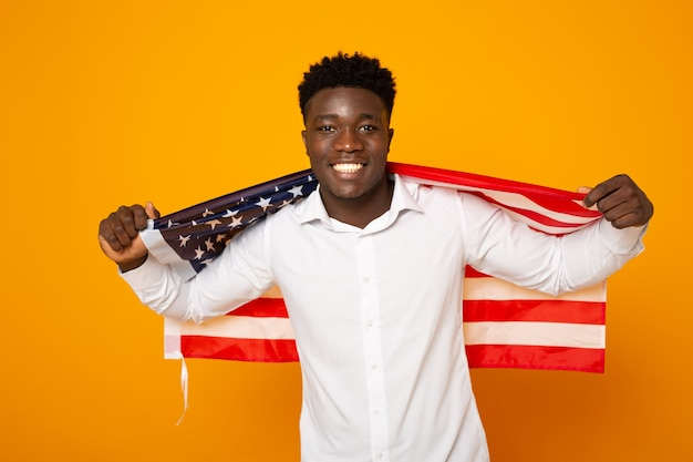 Bonito jovem africano do sexo masculino com bandeira americana em fundo amarelo