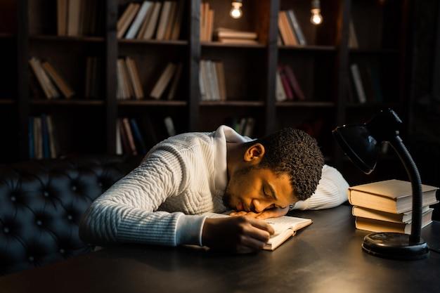 Bonito jovem africano dormindo na mesa com livros