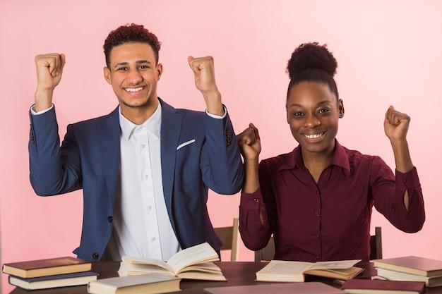 Bonito jovem africano e mulher lendo livros à mesa