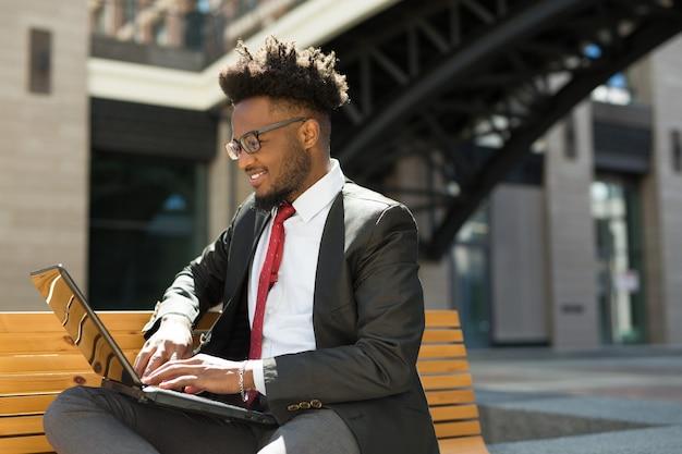 Bonito jovem africano no banco com laptop no verão