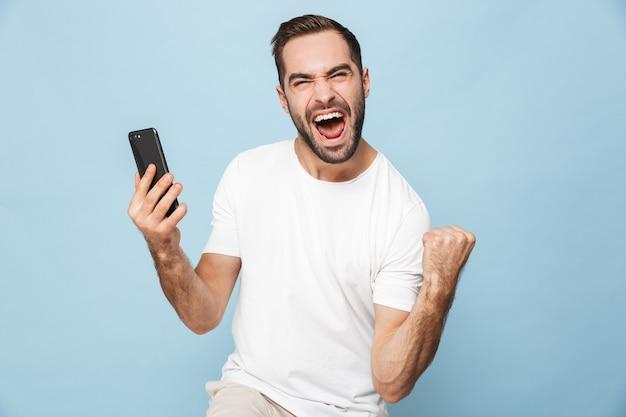 Bonito jovem animado usando telefone celular isolado sobre a parede azul faz gesto de vencedor.