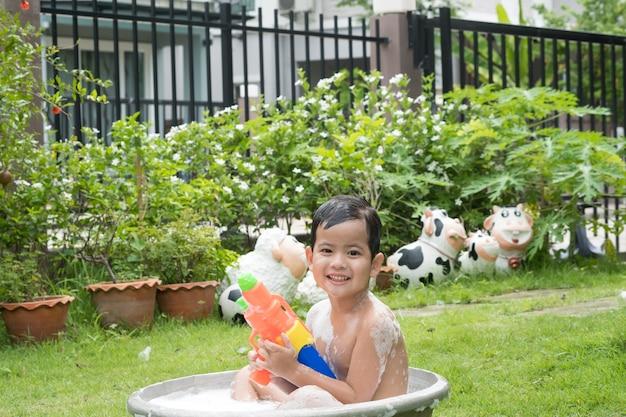 Bonito jovem asiático brincando com bolhas espumosas ao ar livre em uma banheira.