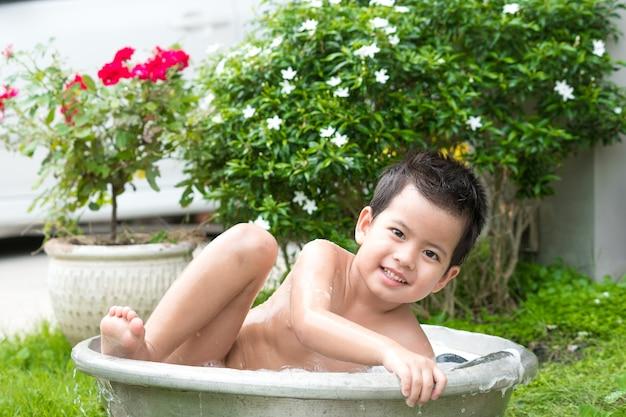 Bonito jovem asiático brincando com bubblesoutdoors em uma banheira.