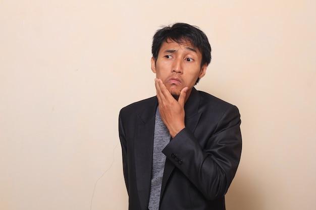 Bonito jovem asiático com expressão pensador está puxando para baixo os lábios, vestindo um terno com