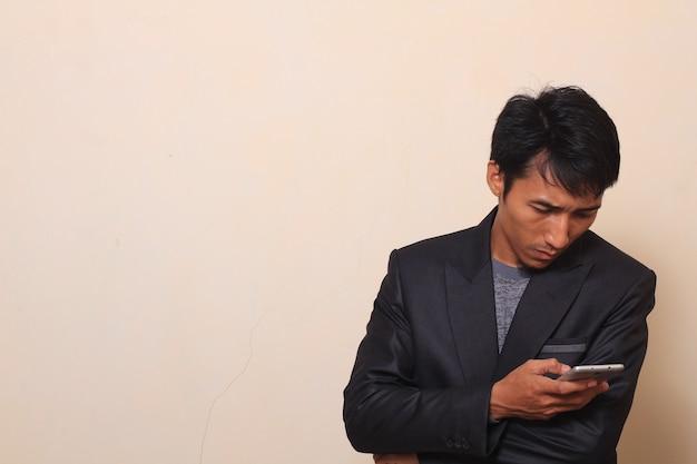 Bonito jovem asiático com expressão preguiçosa pegar um telefonema, vestindo um terno com um swea