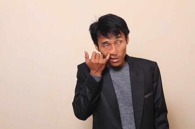 Bonito jovem asiático é dedo no nariz com expressão confortável, vestindo um terno com