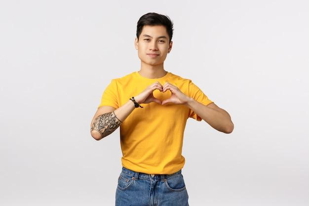 Bonito jovem asiático em camiseta amarela, mostrando sinal de coração