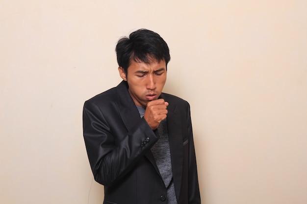 Bonito jovem asiático está tossindo por causa de sua doença, vestindo um terno com uma camisola ins