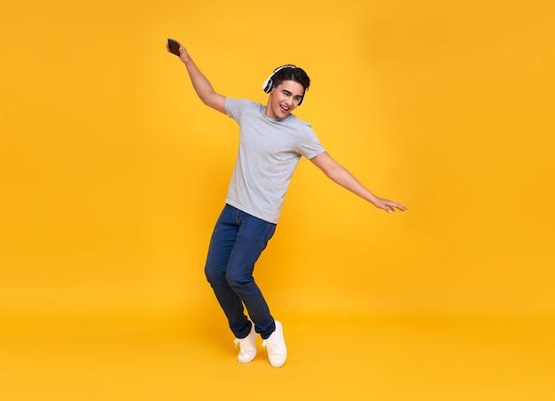 Bonito jovem asiático sorrindo e pulando usando fone de ouvido sem fio, ouvindo música isolada sobre a parede amarela.