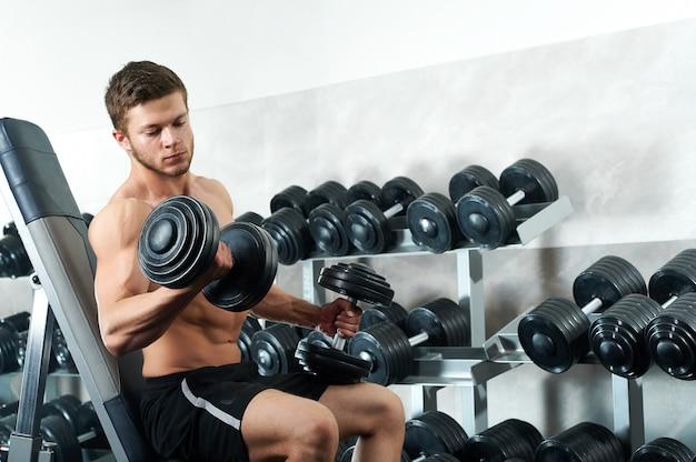 Bonito jovem atleta malhando na academia