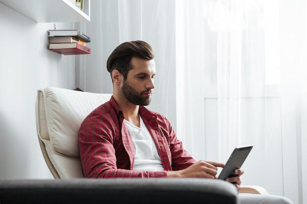 Bonito jovem barbudo usando computador tablet