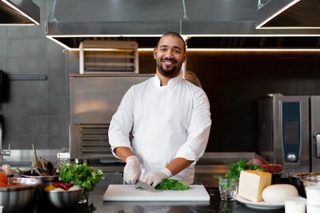 Bonito jovem chef africano em pé na cozinha profissional no restaurante preparando uma refeição de legumes de carne e queijo. retrato de homem em uniforme de cozinheiro corta endro com uma faca de metal.