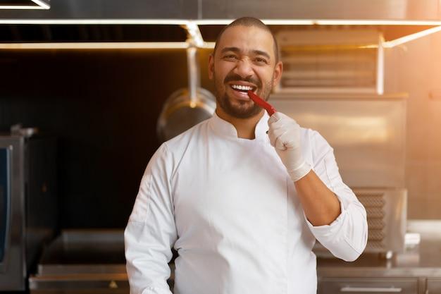 Bonito jovem chef africano em pé na cozinha profissional no restaurante preparando uma refeição de legumes de carne e queijo. retrato de homem em uniforme de cozinheiro. prove pimenta vermelha