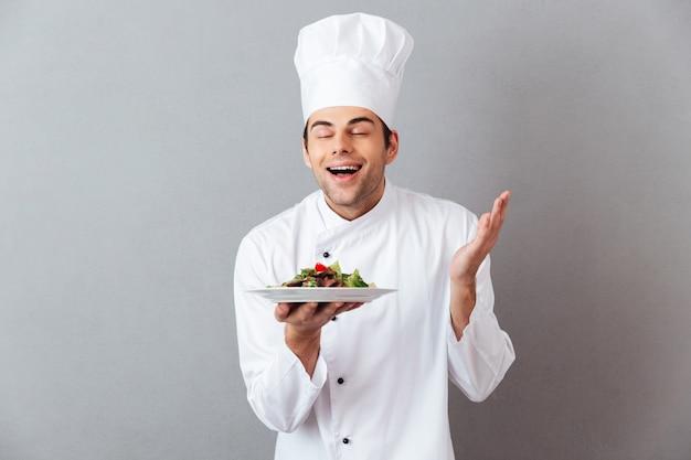 Bonito jovem cozinheiro em salada de cheiro uniforme