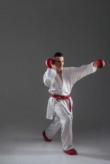 Bonito jovem desportista na prática de quimono no caratê isolado sobre fundo cinza. olhe para o lado.