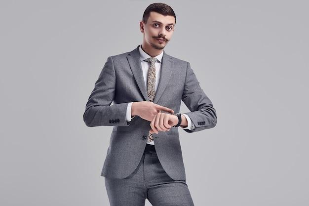 Bonito jovem empresário árabe com bigode no terno da moda cinza