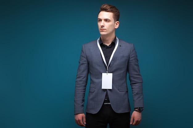 Bonito jovem empresário em jaqueta cinza com cartão de identificação em branco