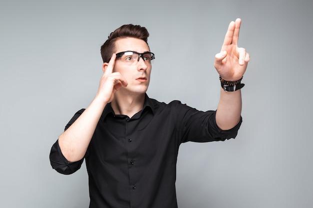 Bonito jovem empresário em relógio caro, óculos e camisa preta
