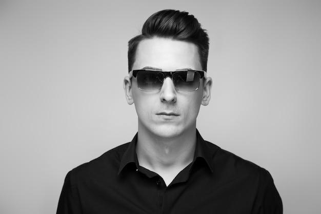 Bonito jovem empresário em relógio caro, óculos escuros e camisa preta