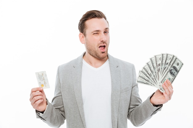 Bonito jovem empresário segurando o cartão de crédito e dinheiro