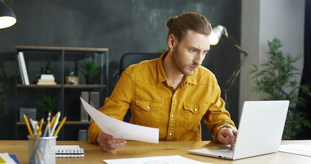 Bonito jovem empresário sentado à mesa no escritório, verificar documentos e trabalhando no laptop.