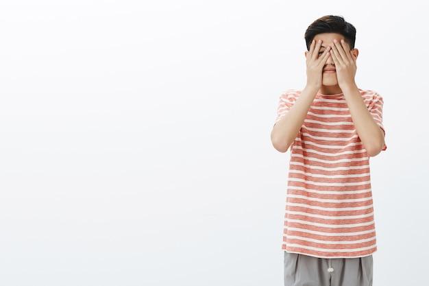 Bonito jovem estudante asiático ansioso para ver o que o destino preparou para ele